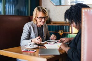 a blonde social security disability lawyer and client talk over papers in a restaurant booth