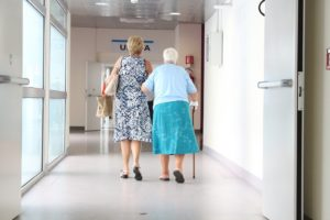 an elderly woman walks down a hospital hall supported by another woman
