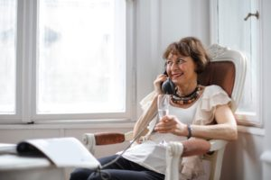 an elderly woman sits in a chair and talks with an administrative law judge on a phone